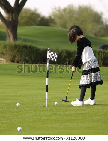 Young girl playing golf - stock photo