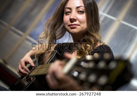 Young girl playing guitar. Used shallow dof and selective focus. - stock photo