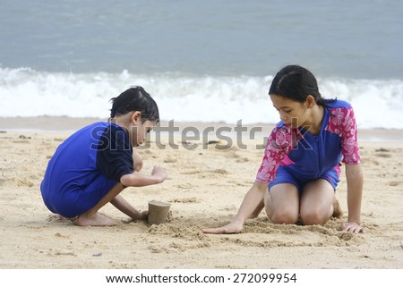 Young girl playing in the sand at the beach with younger brother
