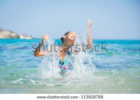 Young girl playing in the wave with spray - stock photo