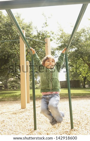 Young girl playing on the monkey bars