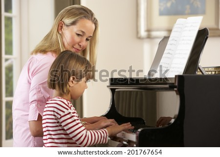 Young girl playing piano in music lesson - stock photo