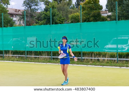 Young girl playing tennis wearing a sportswear on a court outdoor in summer or spring