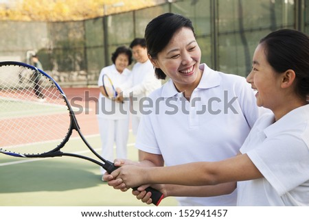 Young girl playing tennis with her coach
