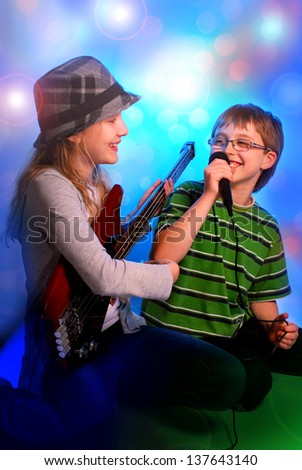 young girl playing the bass guitar and boy singing with microphone on stage - stock photo