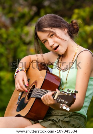 Young girl playing the guitar and singing outdoors - stock photo