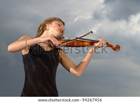 Young girl playing violin over blue sky and cloud