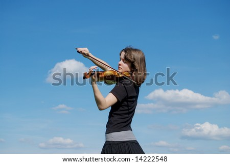 Young girl playing violin over blue sky and clouds