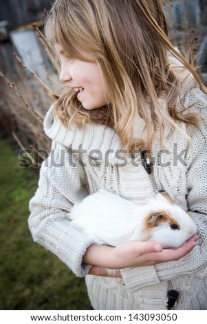 young girl playing with a cavy in the garden