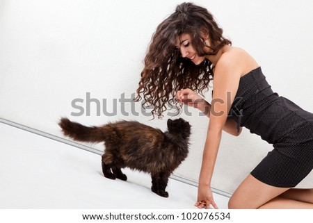 Young girl playing with a kitten in a white room - stock photo