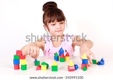 Young girl playing with colorful and educational toy blocks.   - stock photo