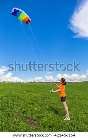 Young girl playing with colorful kite on the green hill