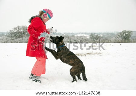 Young girl playing with her dog in the snow - stock photo