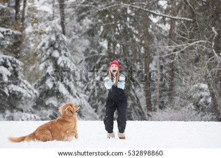 Young girl playing with her golden retriever dog in the winter s