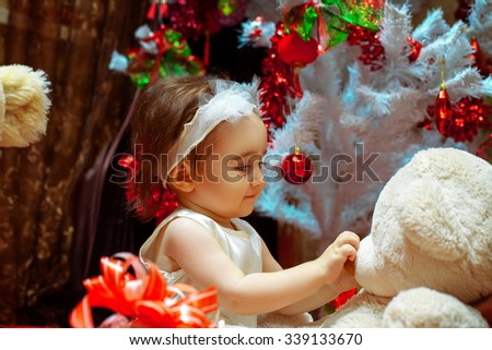 Young girl playing with her teddy bear under white Christmas tree. Christmas mood, New year. - stock photo