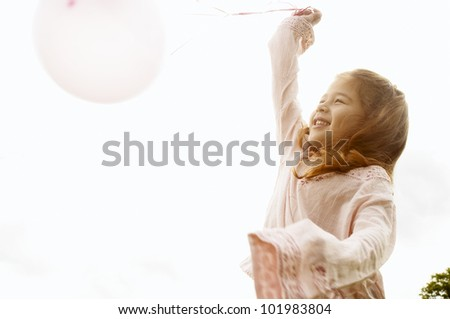 Young girl playing with pink balloons and smiling in the park. - stock photo