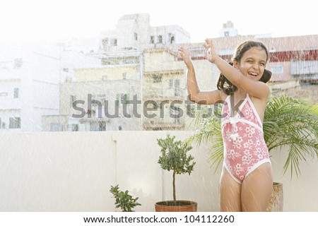 Young girl playing with water on a terrace in the city during the summer vacation.