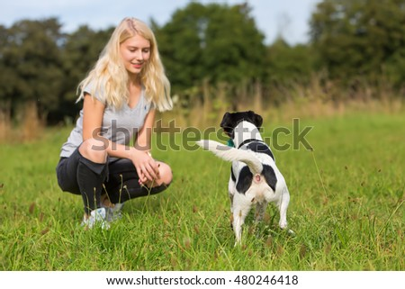 young girl plays with a Parson Russell Terrier