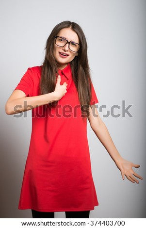Young girl pointing questioningly at herself with   Who, me? expression. Surprised, little girl getting unexpected attention from people, asking you talking to, mean me? on grey background. - stock photo