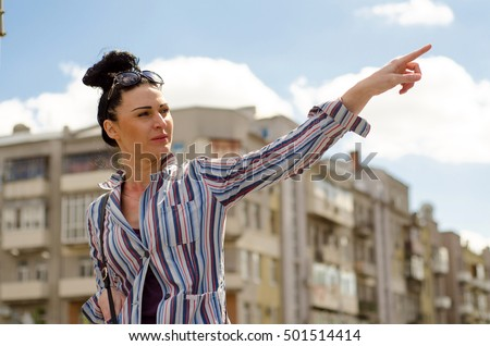 young girl pointing to the other side in the street