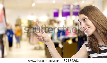 young girl pointing up in a shopping center