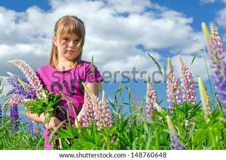 Young girl portrait in lupine flowers field - stock photo