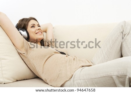 young girl portrait lying on a sofa, listen music in headphones. indoor relax at home. beautiful woman. smiling and happy
