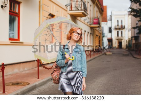 young girl poses on the street wearing glasses and umbrella - stock photo