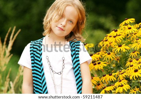 Young girl posing around flowers - stock photo