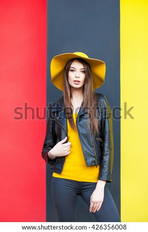Young girl posing by the color wall - stock photo