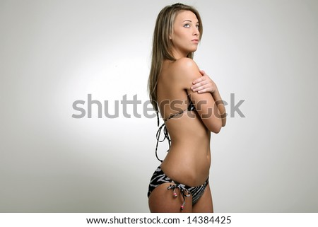 Young girl posing in bikini on a white background.