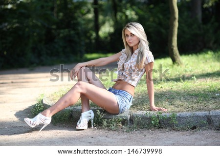 Young girl posing in the park and on the beach