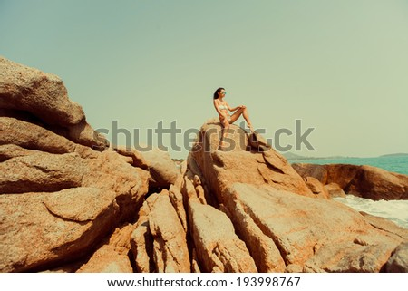 Young girl posing near rock