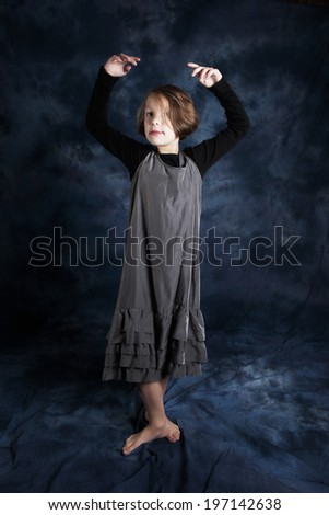 Young girl posing some of her ballet stances against a dark navy blue background.
