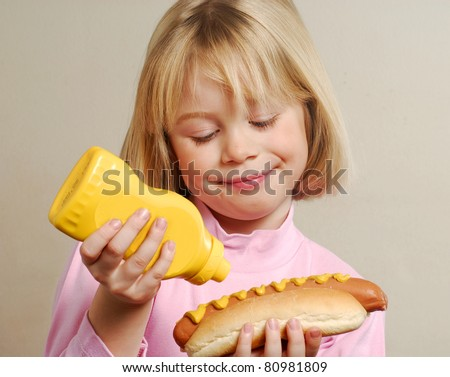 Young girl pouring mustard on her hot dog. - stock photo