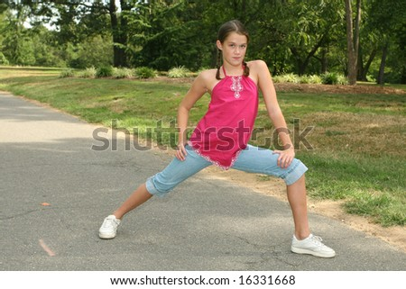 Young girl practicing dance moves or stretching on a path in a park, outdoor setting