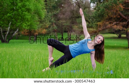 Young girl practicing yoga in nature in the woods on a background of green trees and grass.