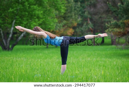Young girl practicing yoga in nature in the woods on a background of green trees and grass. She balances on one leg.
