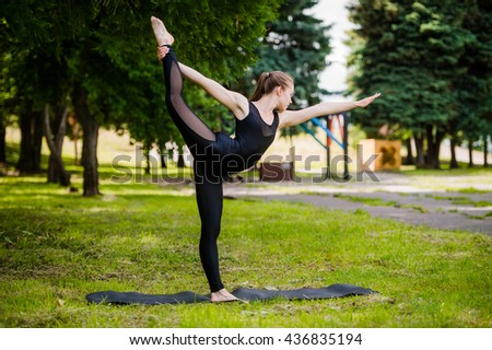 Young girl practicing yoga in nature in the woods on a background of green trees and grass. She balances on one leg. - stock photo