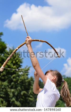 Young girl practising archery standing aiming her bow and arrow up into the sky in the countryside - stock photo