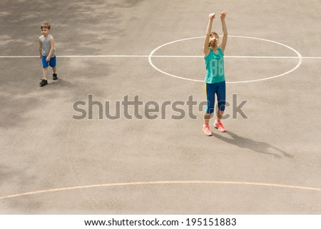 Young girl practising on a basketball court throwing the ball as a small boy saunters past alongside her