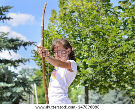 Young girl practising with a homemade bow and arrow carefully taking aim at her target - stock photo