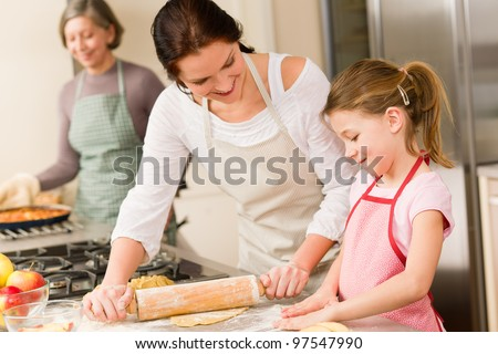 Young girl prepare apple pie baking with mother and grandmother - stock photo