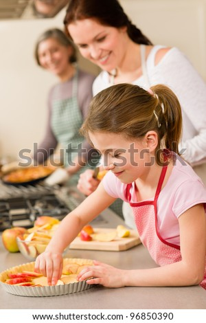 Young girl prepare apple tart baking with mother and grandmother - stock photo