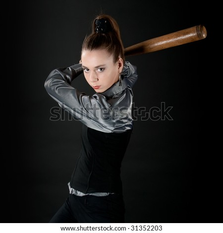 Young girl prepares to strike by baseball bat - stock photo