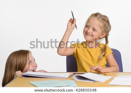 Young girl prepares to throw a pencil she holds in her hand. Pleasant childish smiles and fiery eyes. The elder girl hides under the desk. - stock photo
