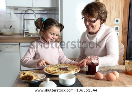 Young girl preparing crepes with her grandmother - stock photo