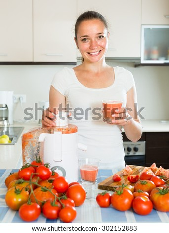 young girl preparing fresh juice in domestic kitchen