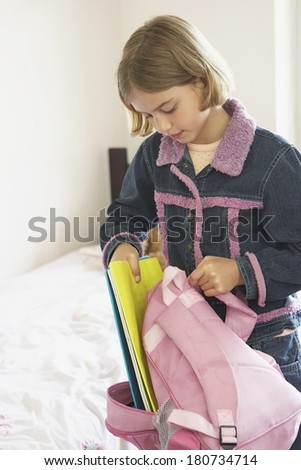 Young girl preparing her bag for school in the morning - stock photo