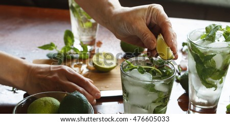 Young girl preparing homemade mojito cocktail, alcoholic or non-alcoholic cocktail, closeup